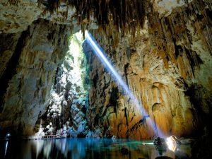 caverna com feixe de luz entrando, lago de águas cristalinas